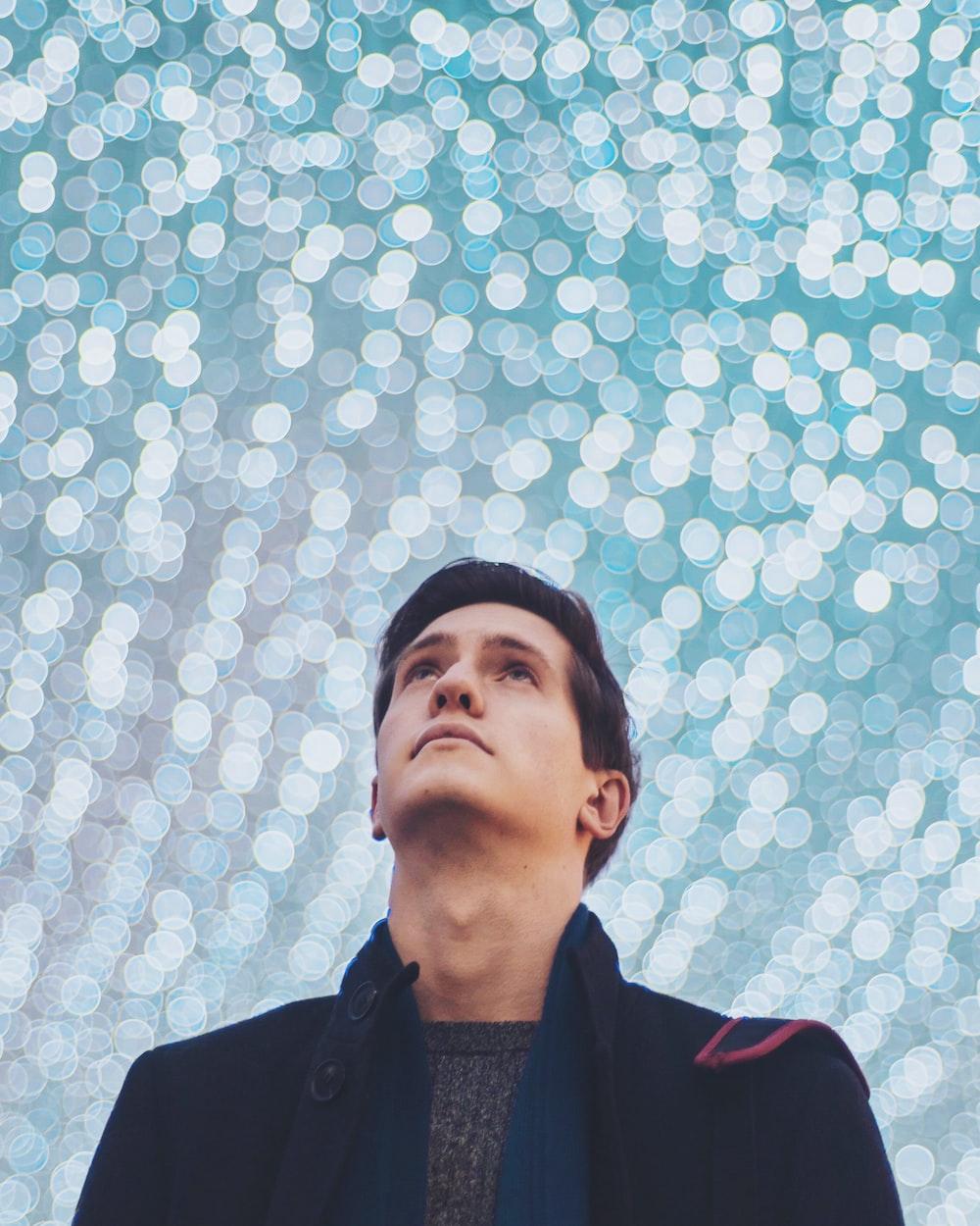 man in black coat looking up