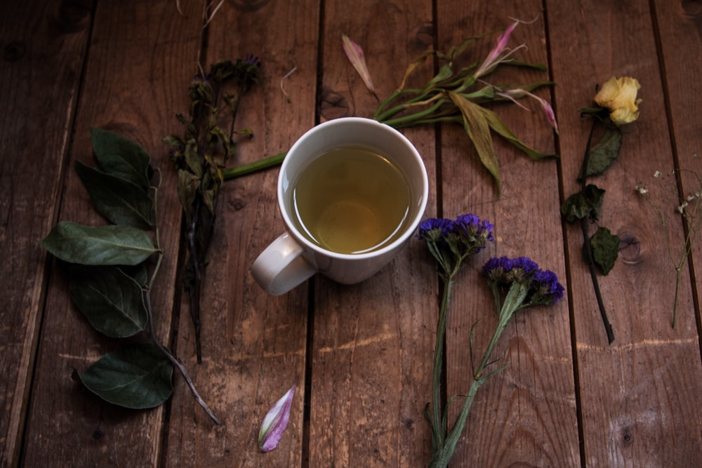white ceramic mug with tea on wooden surface beside green leaf plants and petaled flowers