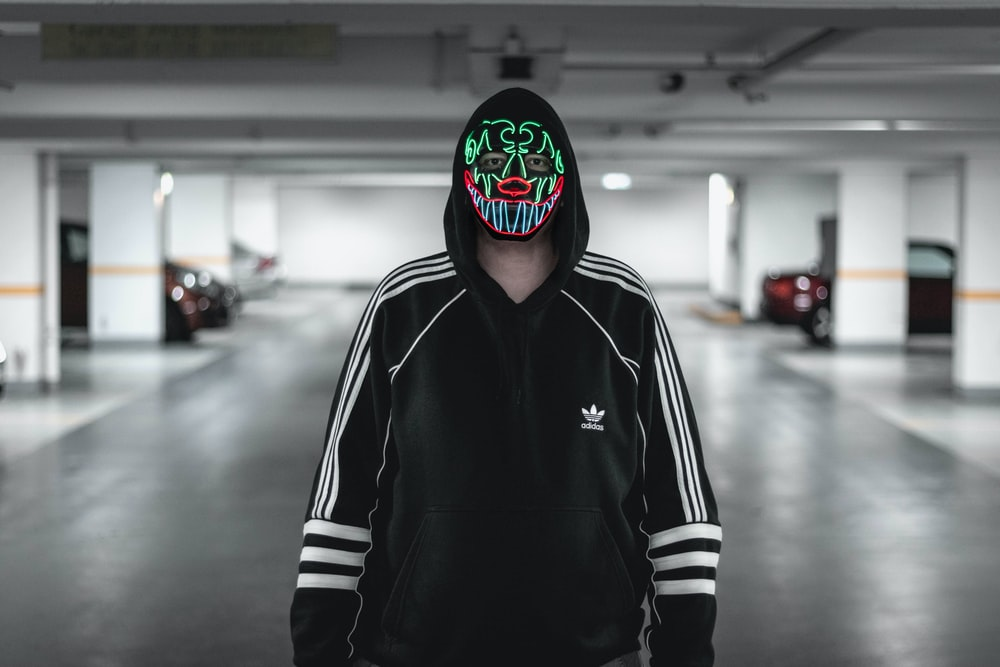 man wearing black and white adidas jacket wearing multicolored mask