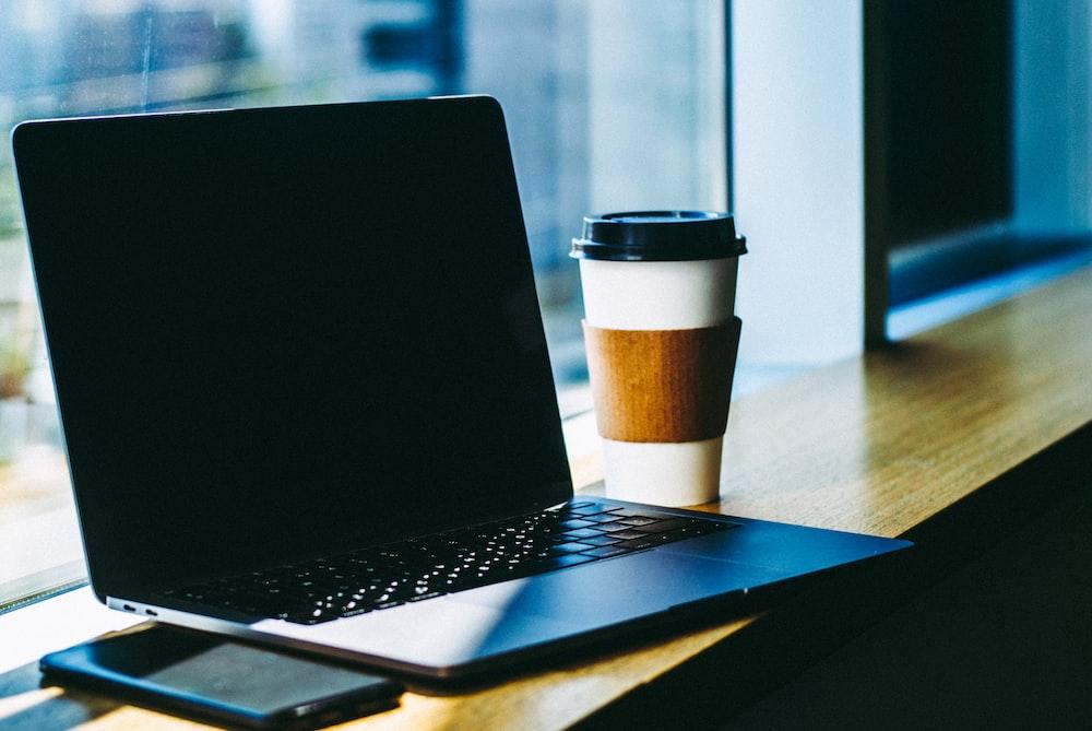 茶色の木製のテーブルに黒いラップトップコンピューター