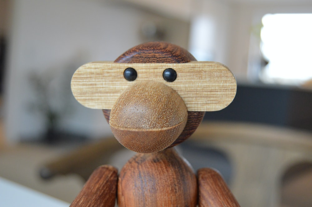 brown wooden monkey figurine in close-up photo