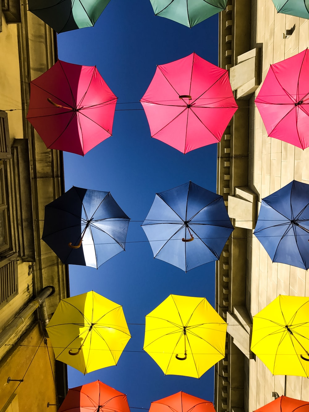 green, pink, blue, yellow, and orange umbrellas hanging in between buildings