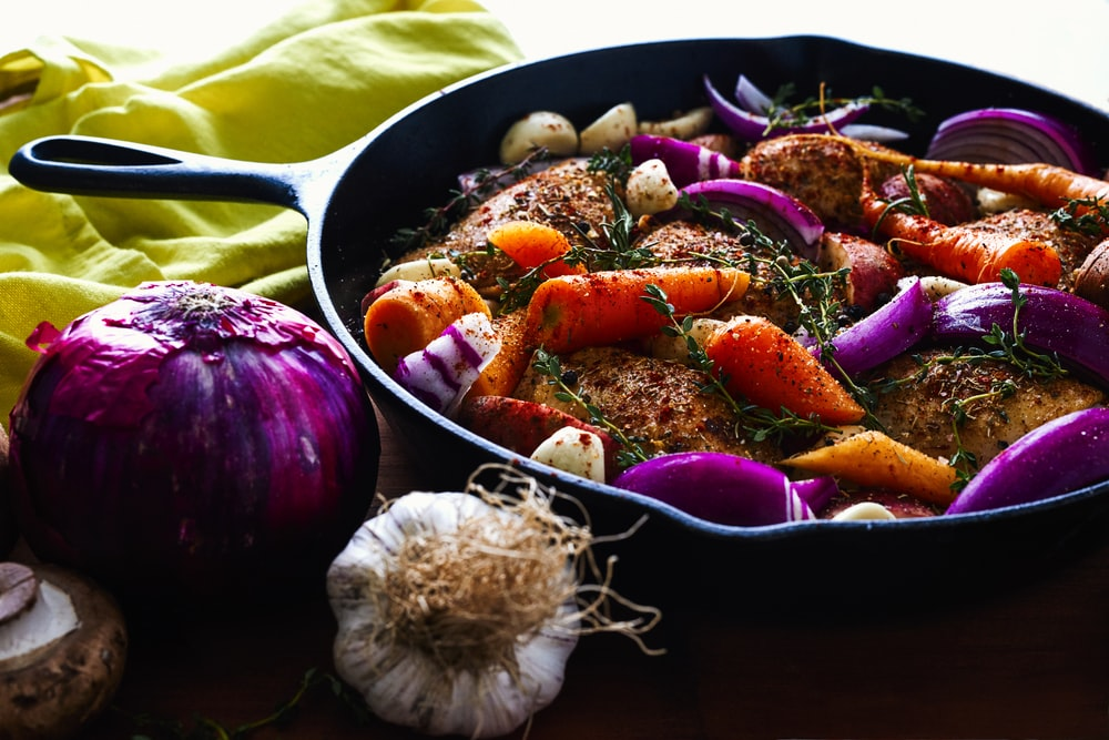 carrots, garlic, onions, and herb spicing meat on skillet