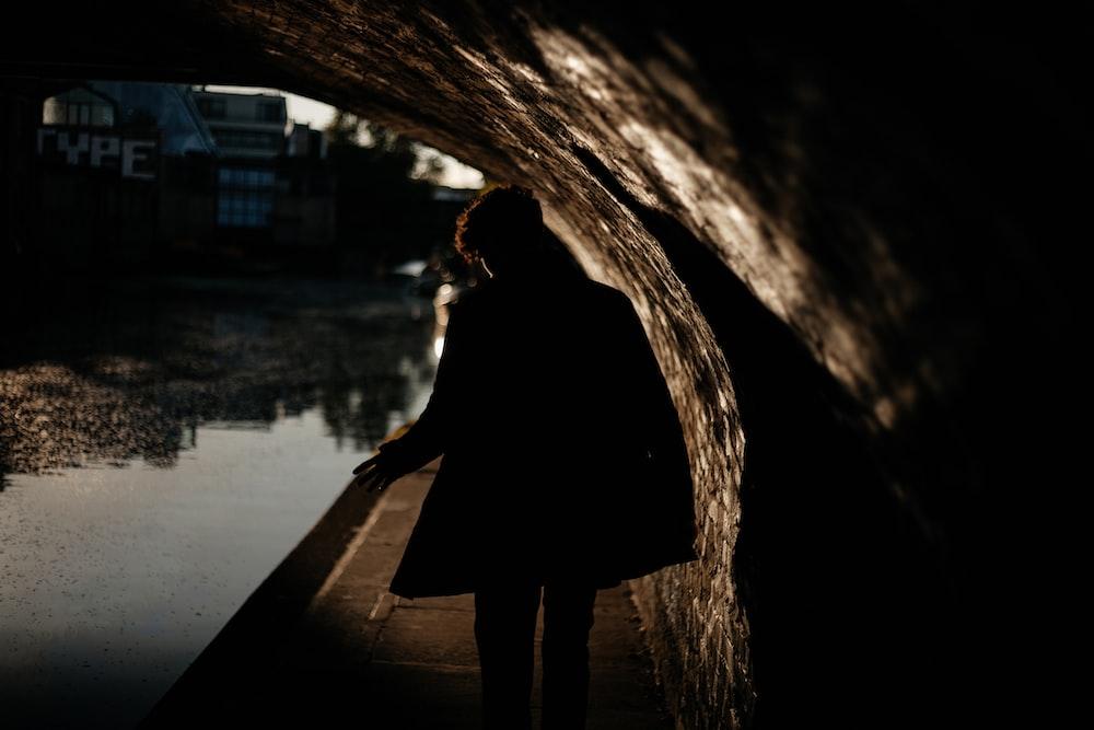 person wearing black coat walking under the bridge