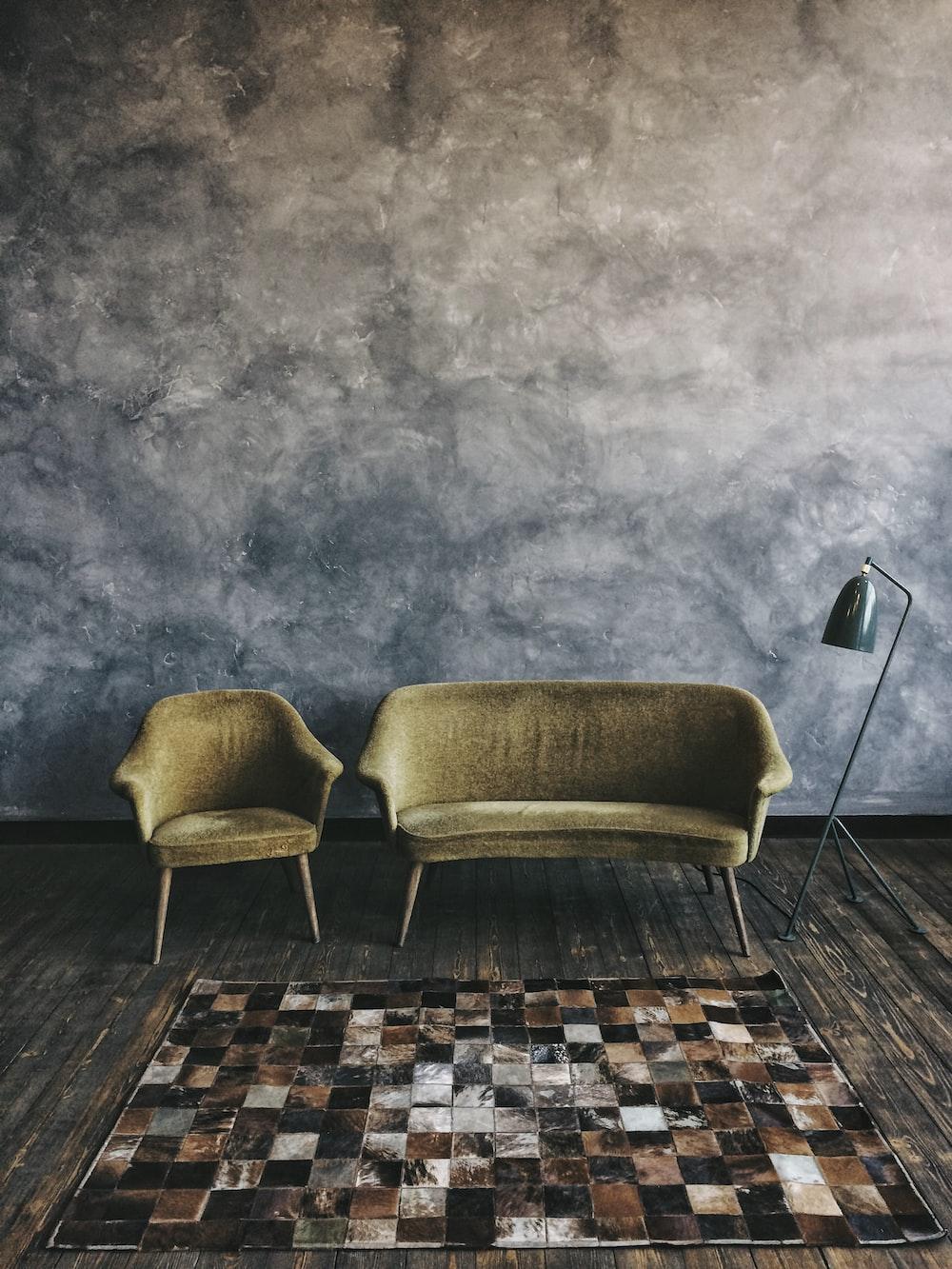 brown sofa and sofa chair beside floor lamp
