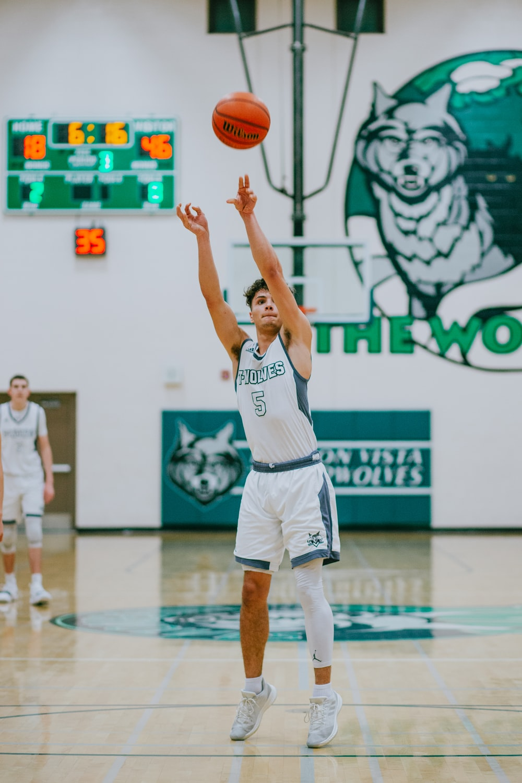 man throwing basketball inside court