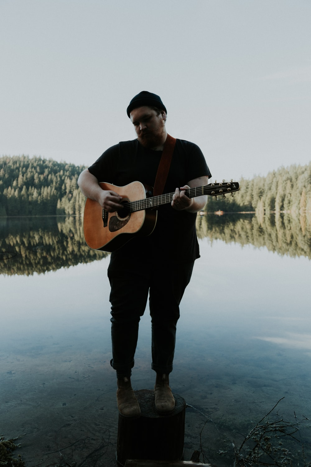 man standing on wooden post playing guitar
