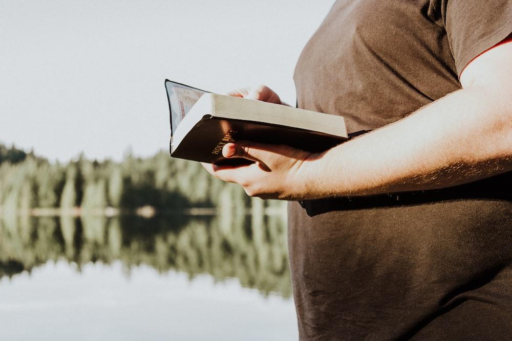 man holding brown book