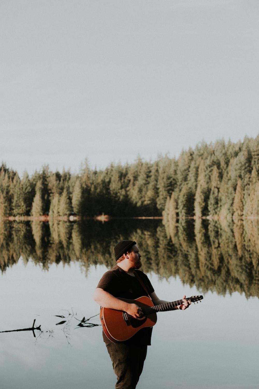 man half soak in body of water playing guitar