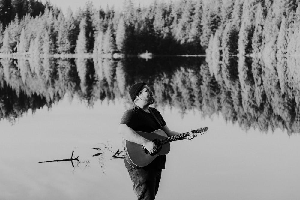 grayscale photo of man playing acoustic guitar