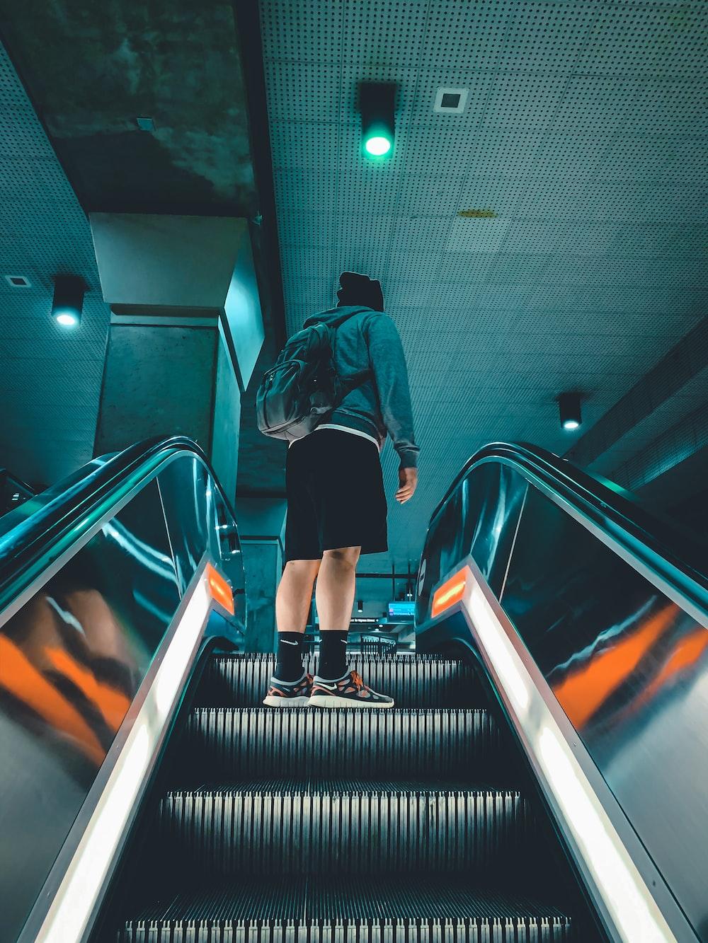 man in jacket standing on escalator