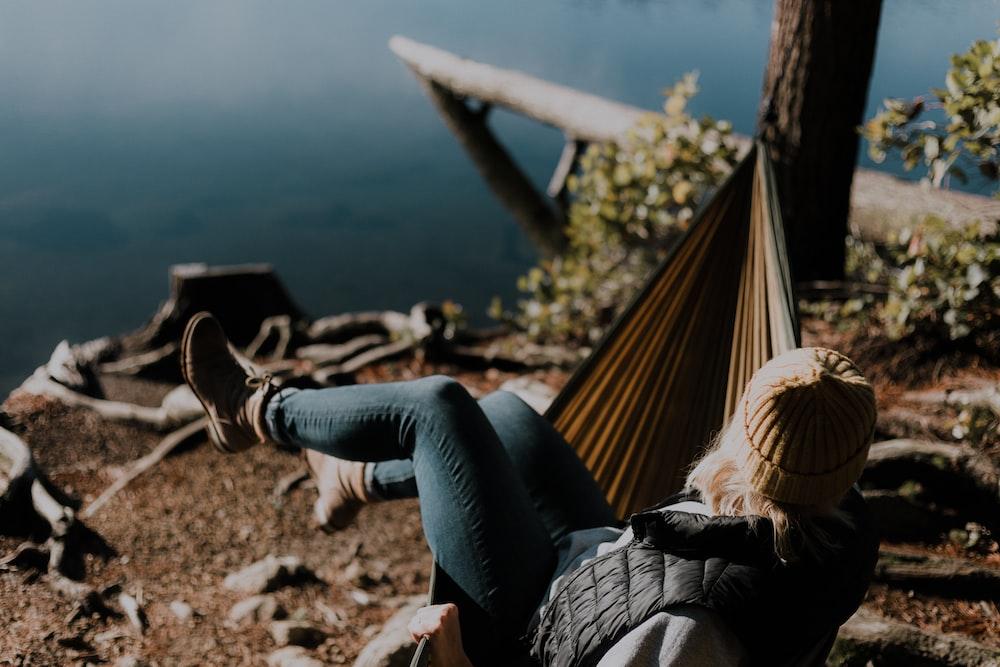 woman sitting on hammock beside calm water