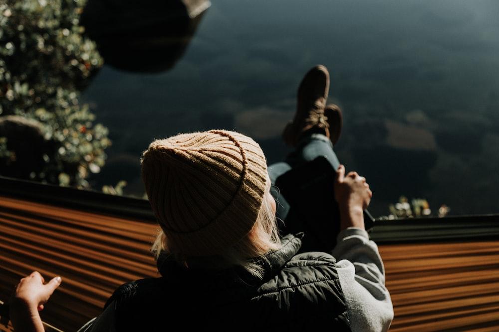 woman sitting on brown hammock