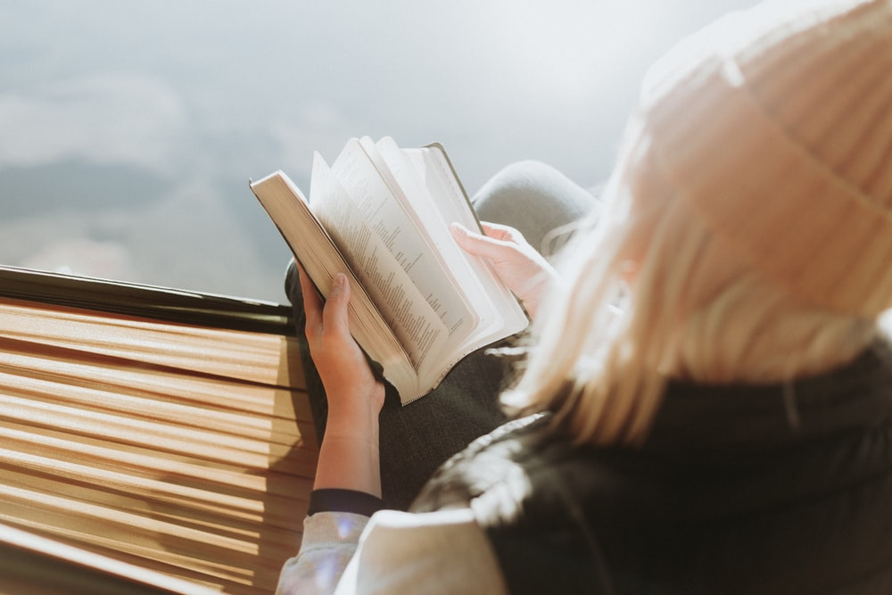 woman sitting on brown ledge while holding book