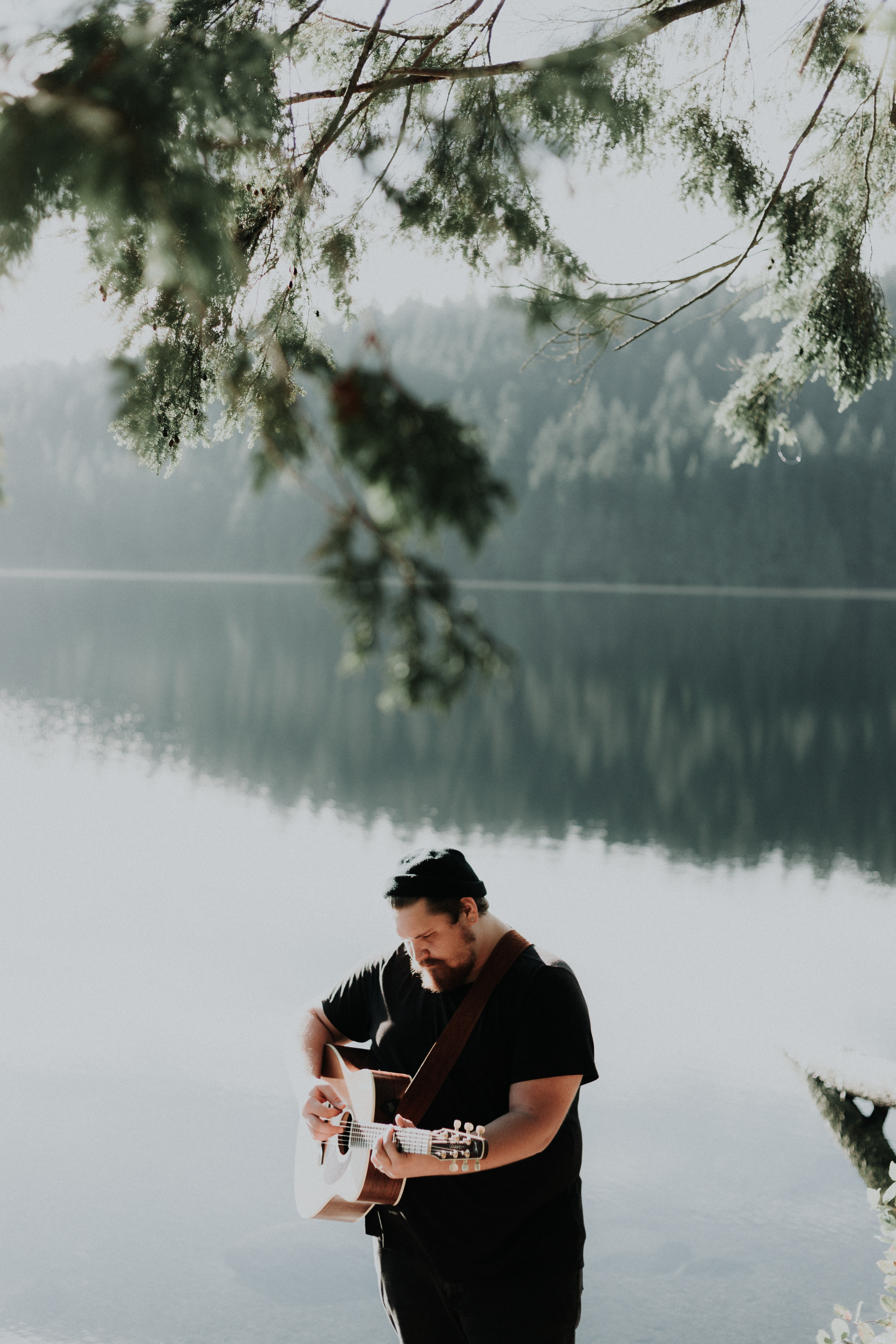 man playing brown acoustic guitar near body of water