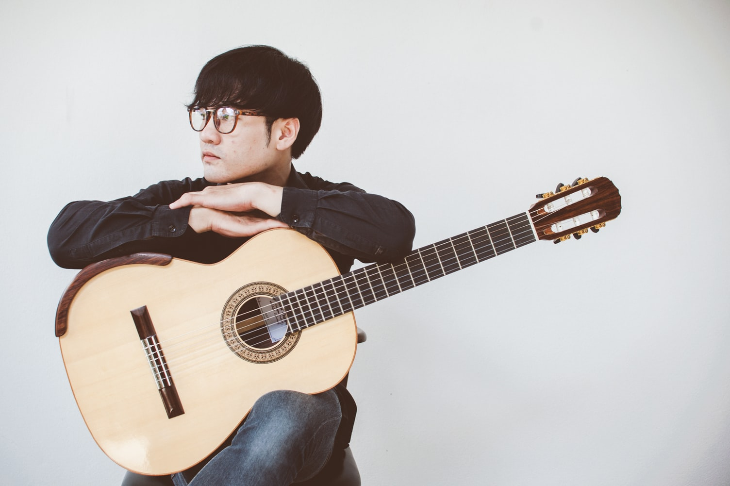 Man wearing a glasses is holding a guitar