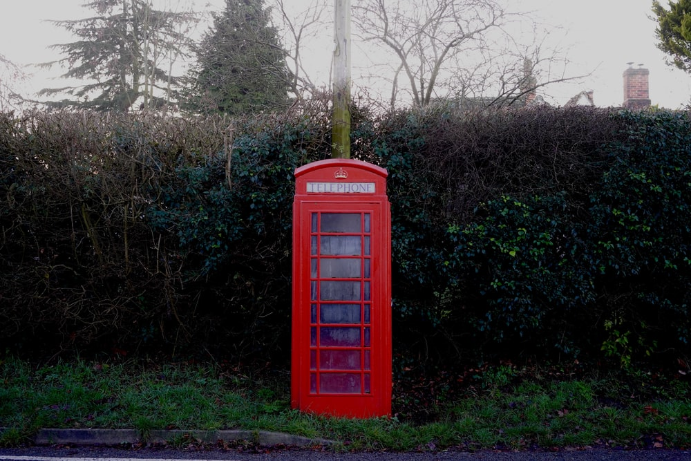 red telephone booth in front of green topiary
