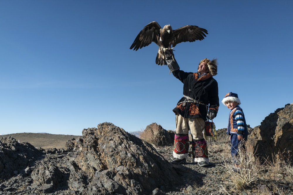 Native American man standing while holding eagle