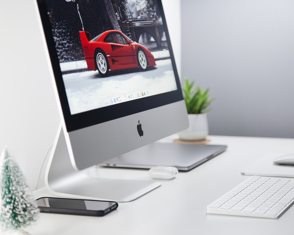 turned-on silver iMac displaying red coupe parked on pavement wallpaper