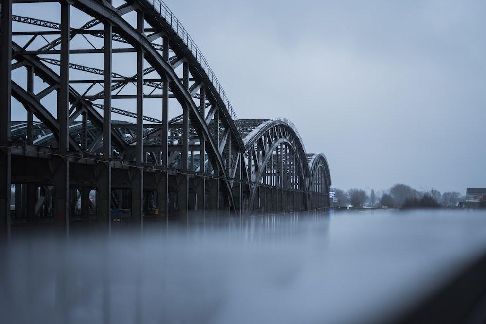 grayscale photography of metal bridge ]