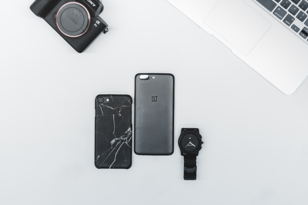 post-2017 black iPhone beside black watch on white surface