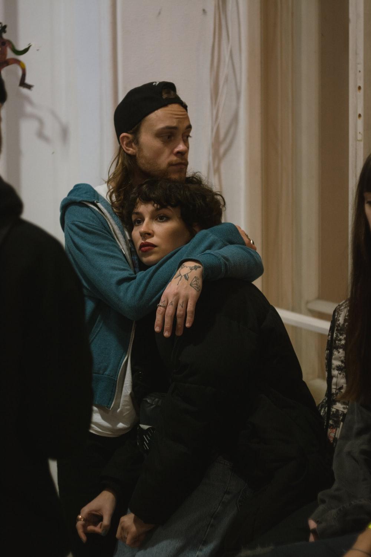 man in blue jacket hugging woman in black jacket
