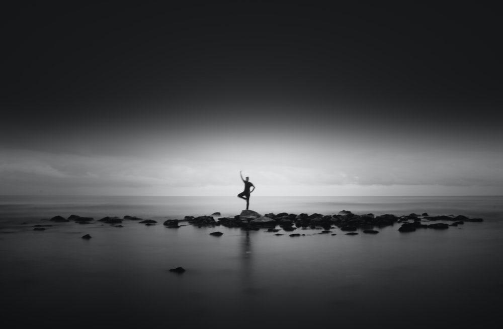 silhouette photo of person at middle of sea