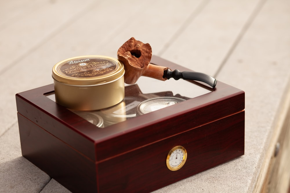 tobacco pipe and herb grinder on brown box