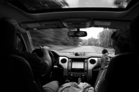 grayscale photography of two persons inside vehicle