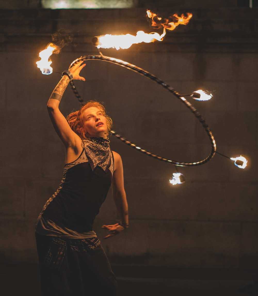 woman fire dancing with hoop during nighttime