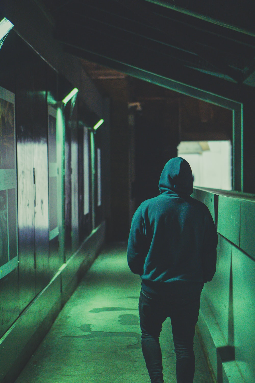 man wearing hoodie walking near wall