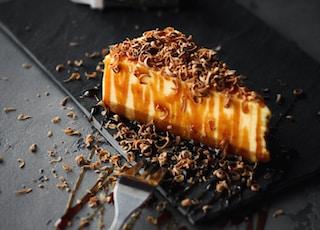 slice of caramel cake on black plate beside fork