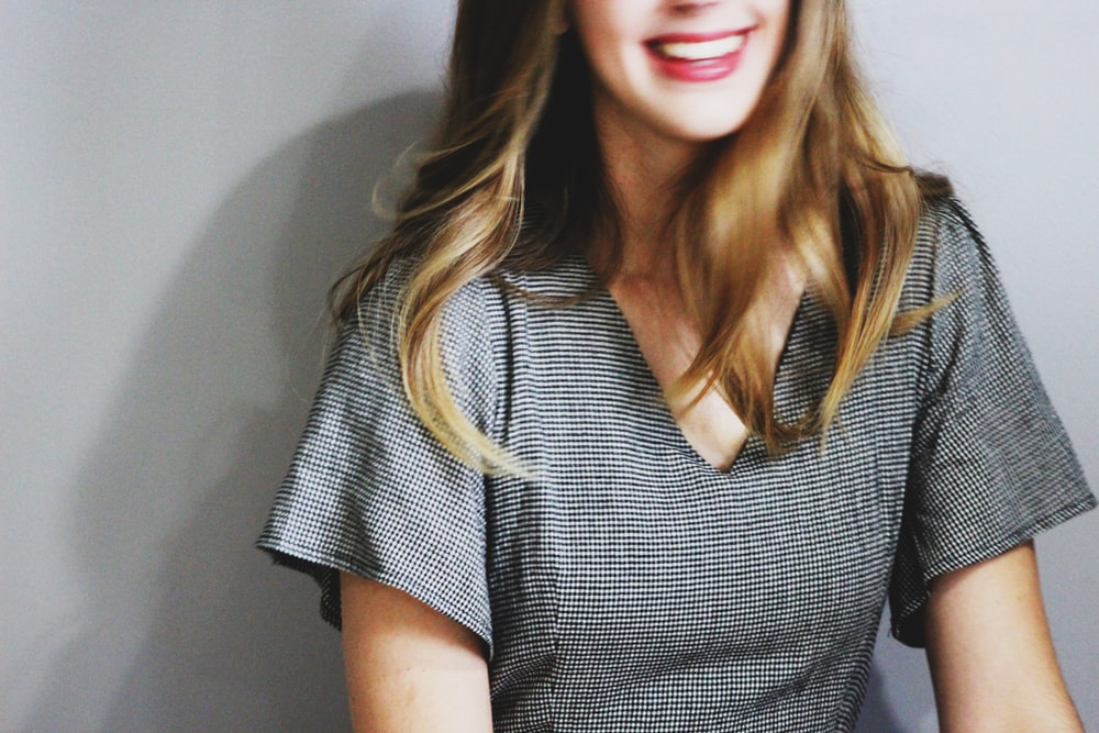 smiling woman wearing gray V-neck blouse