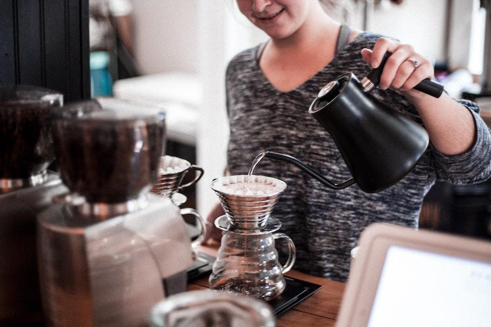 woman pouring tea on teacup using teapot