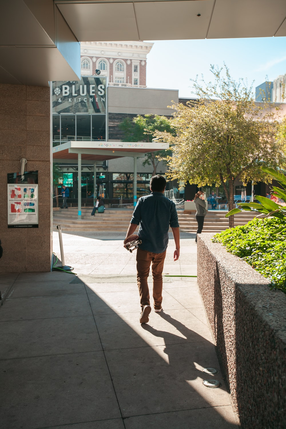 man in gray shirt walking by building during daytime