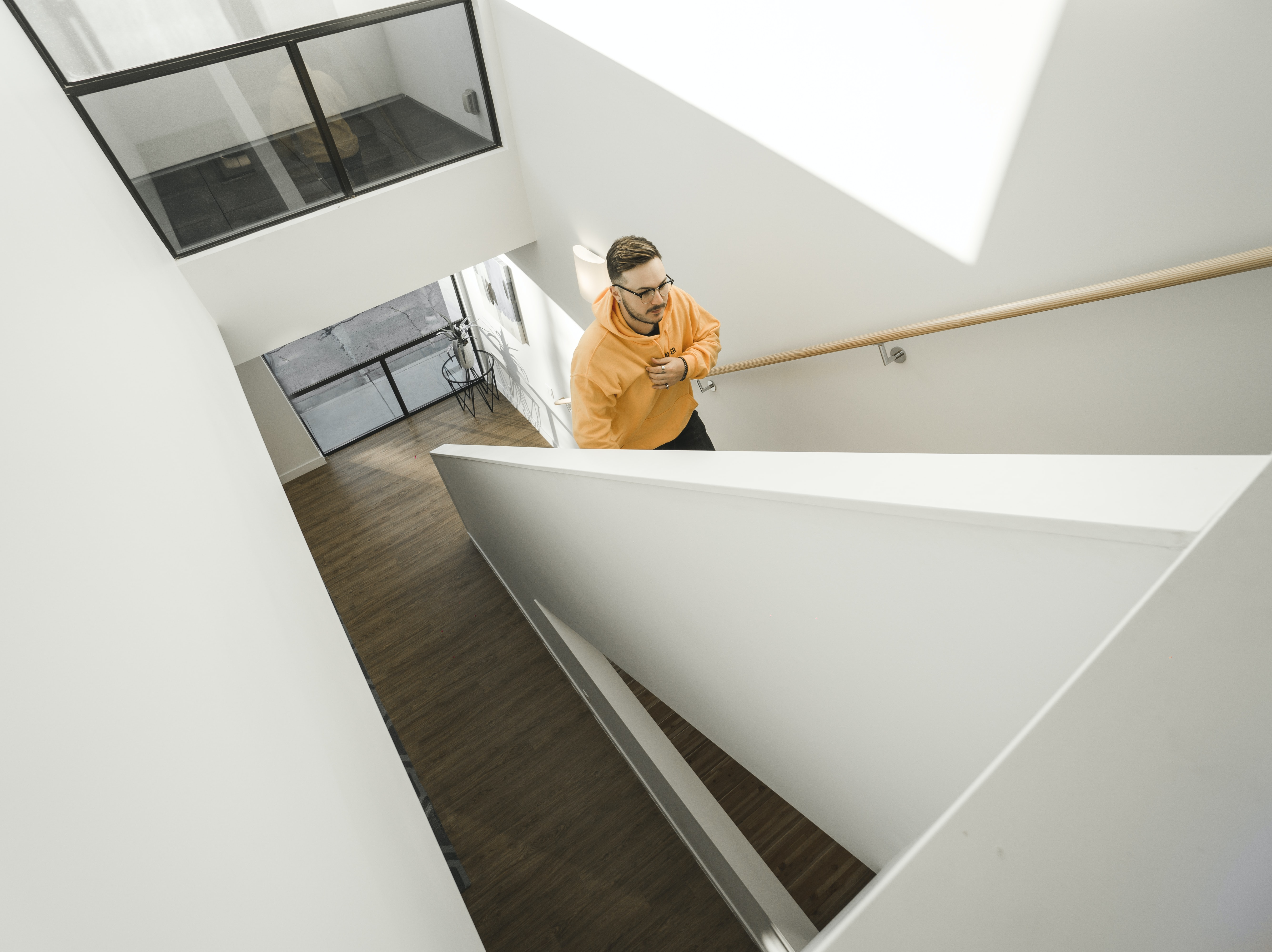 man wearing yellow pullover hoodie climbing on stairs