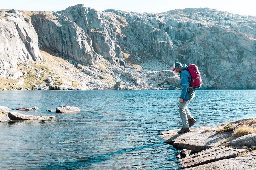 man looking at blue river