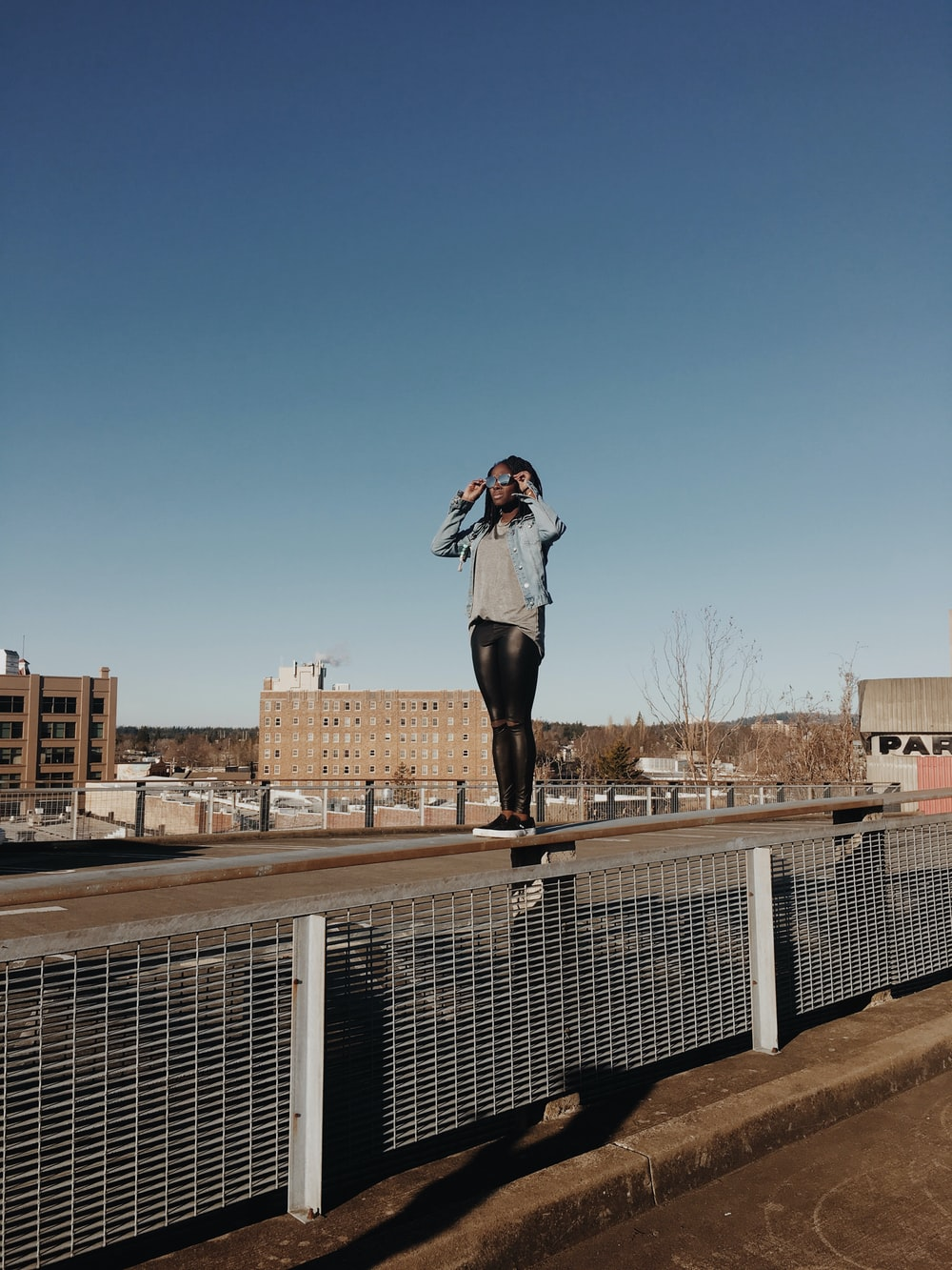 woman standing on fence during daytime