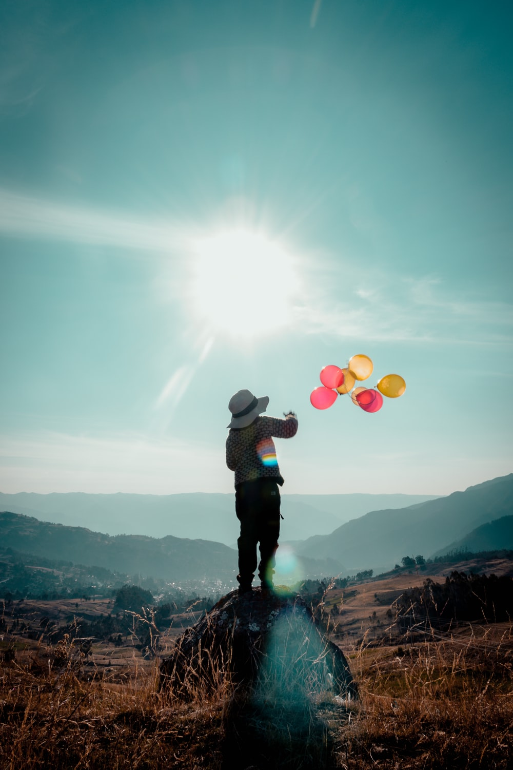 balloons flying near person standing on rock