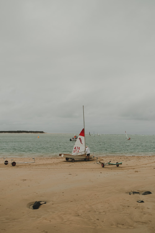 man fixing sailboat at the beach