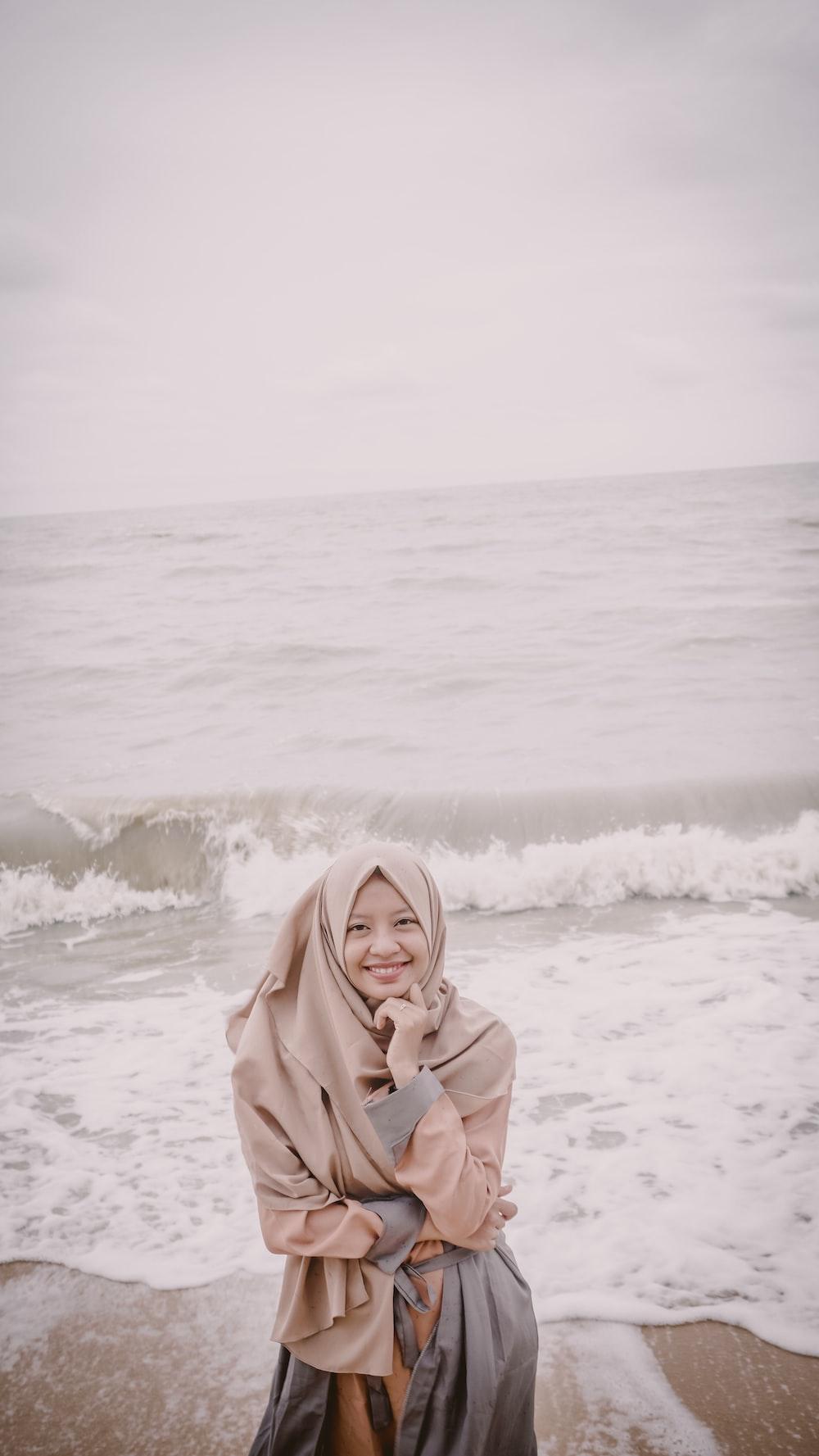woman wearing brown hijab beside seashore