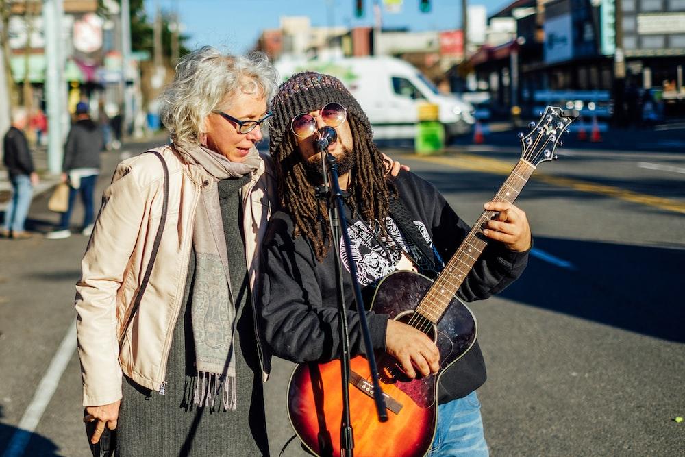 man singing on the street while playing guitar