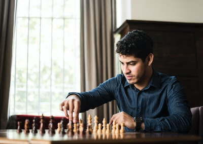 man in blue dress shirt sitting down and playing chess game