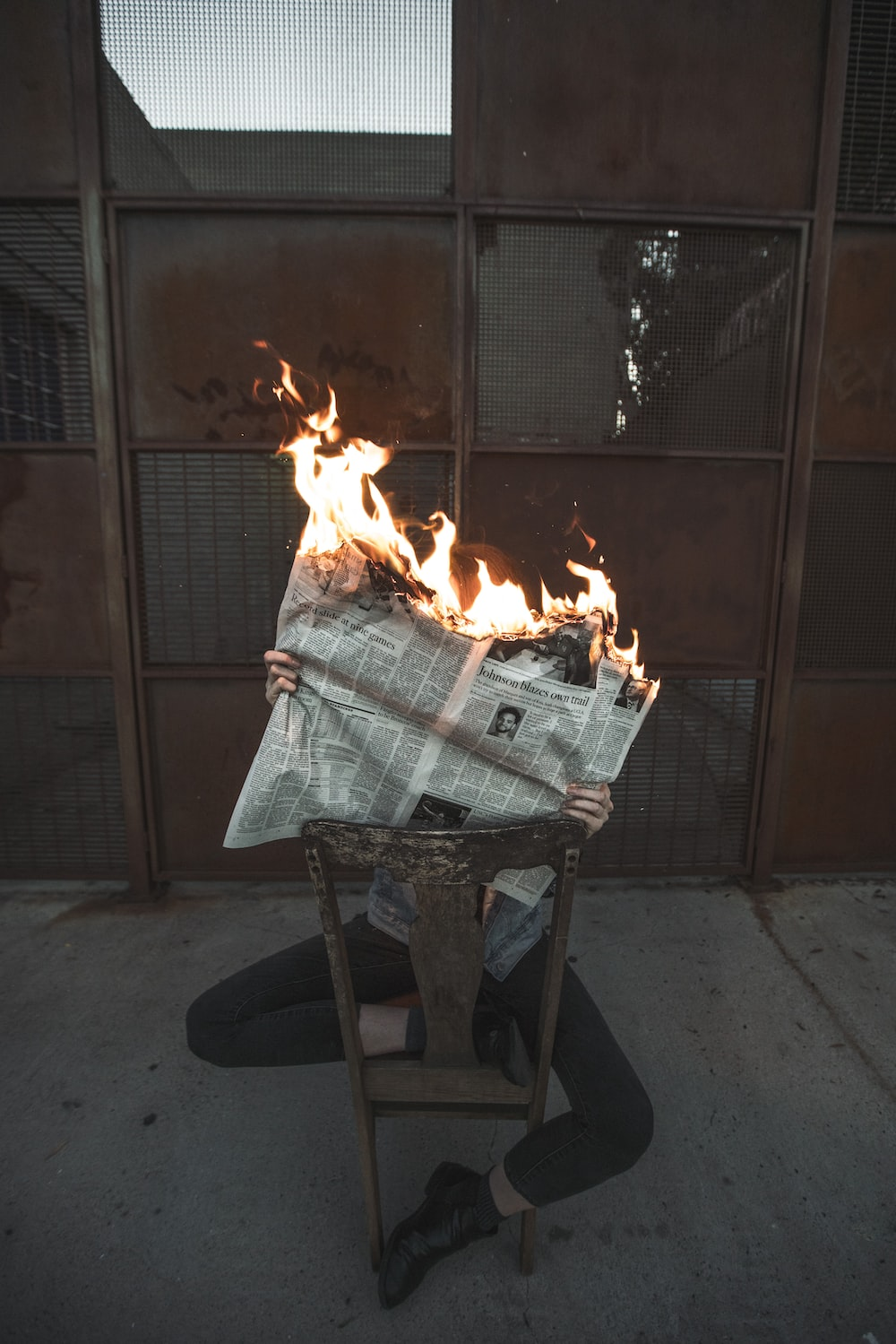 person holding burning newspaper while sitting on wooden chair