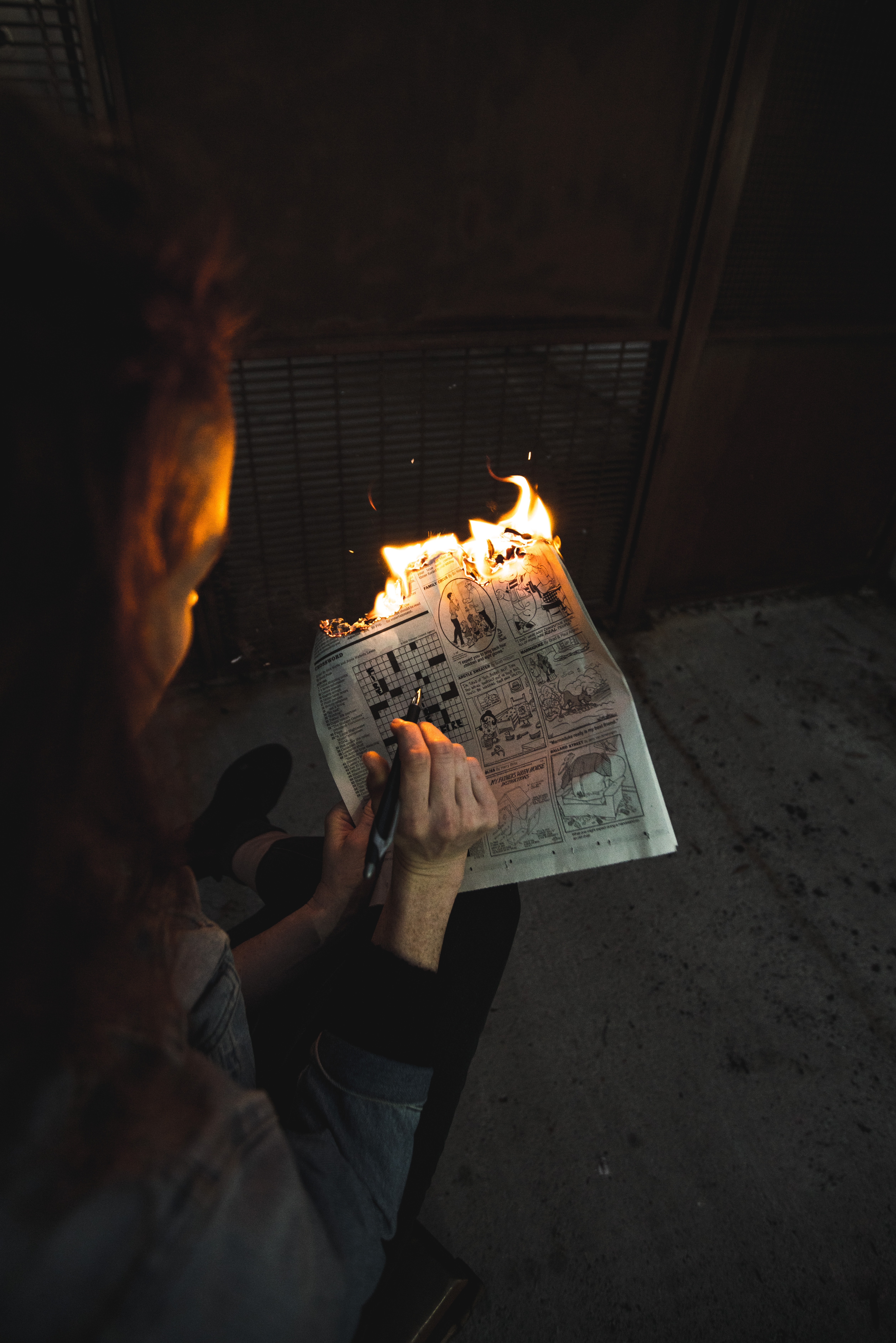 person burning newspaper page