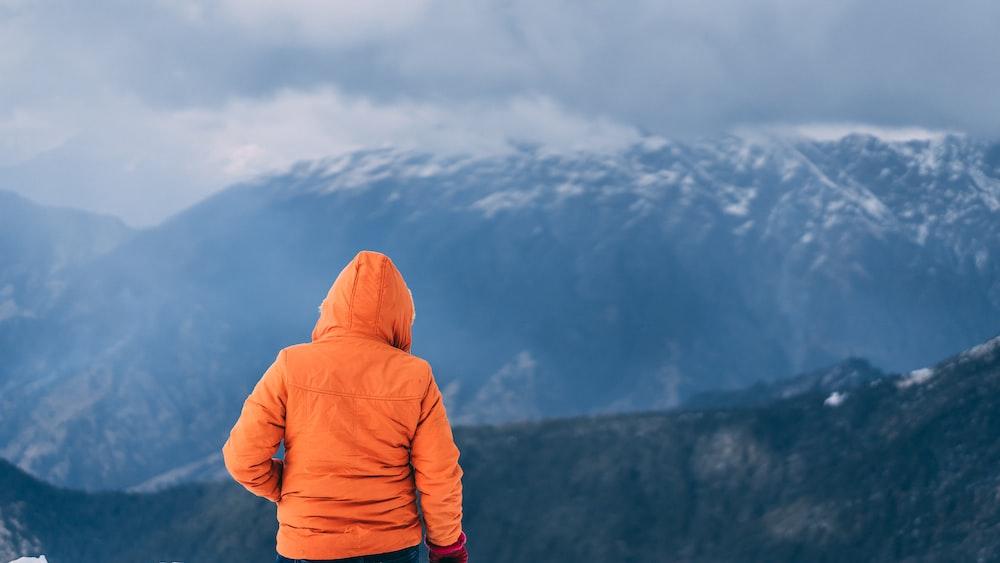 person wearing orange hoodie standing on mountain