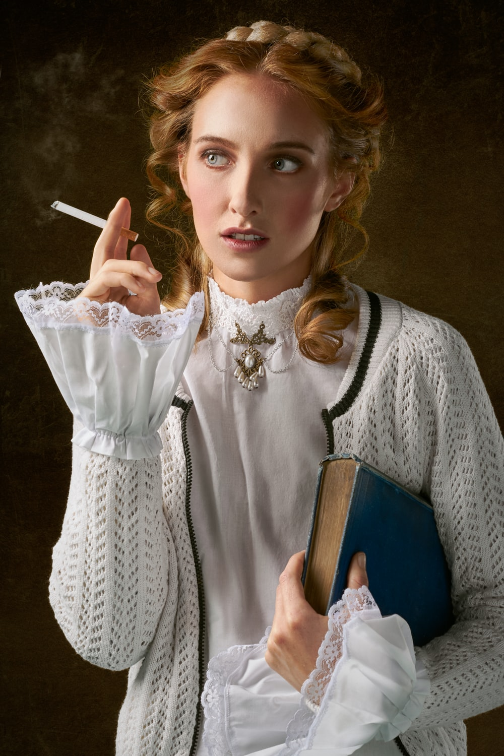 woman with cigarette holding book photo