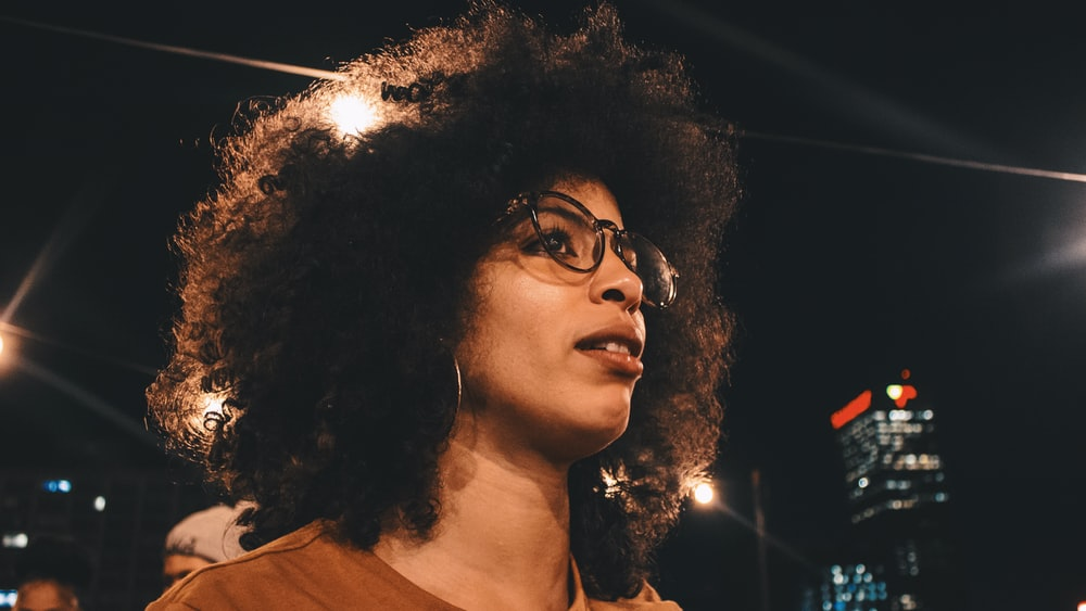 selective focus photography of woman wearing brown crew-neck top and black framed eyeglasses at night