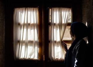 woman holding window curtain