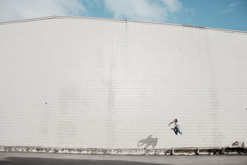 man jumping beside white concrete building
